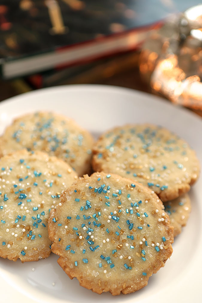Round Sugar Cookies decorated with blue, gold and white sugars.