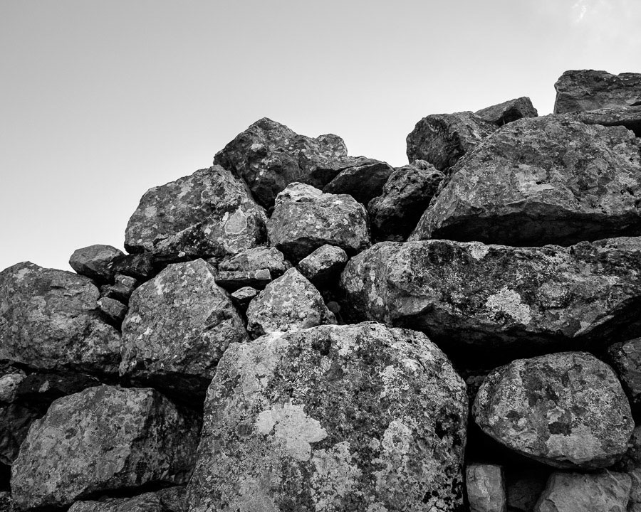 Black and white landscape photo of stone wall in Roman ruins, Spain