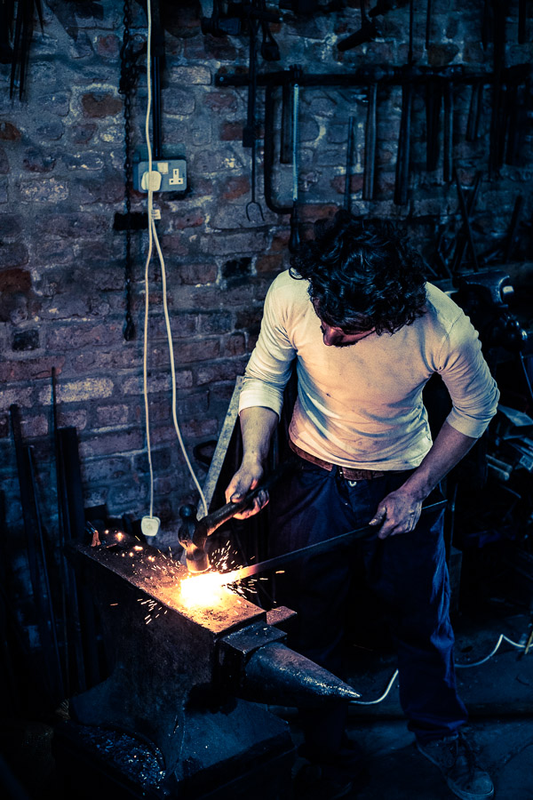 Portrait of blacksmith at work with anvil and hammer