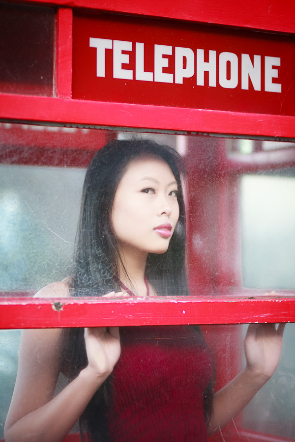Moody color portrait of woman in red telephone box