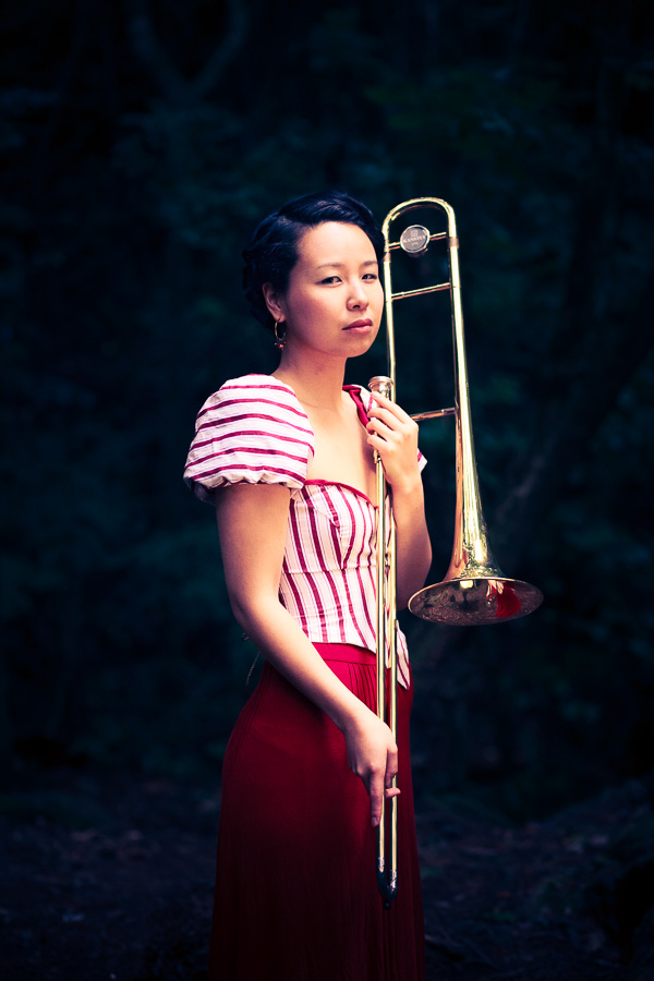 Moody color portrait of a woman with a trombone