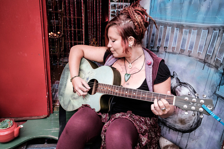 Portrait of woman sitting on doorstep of gypsy caravan and playing a guitar.
