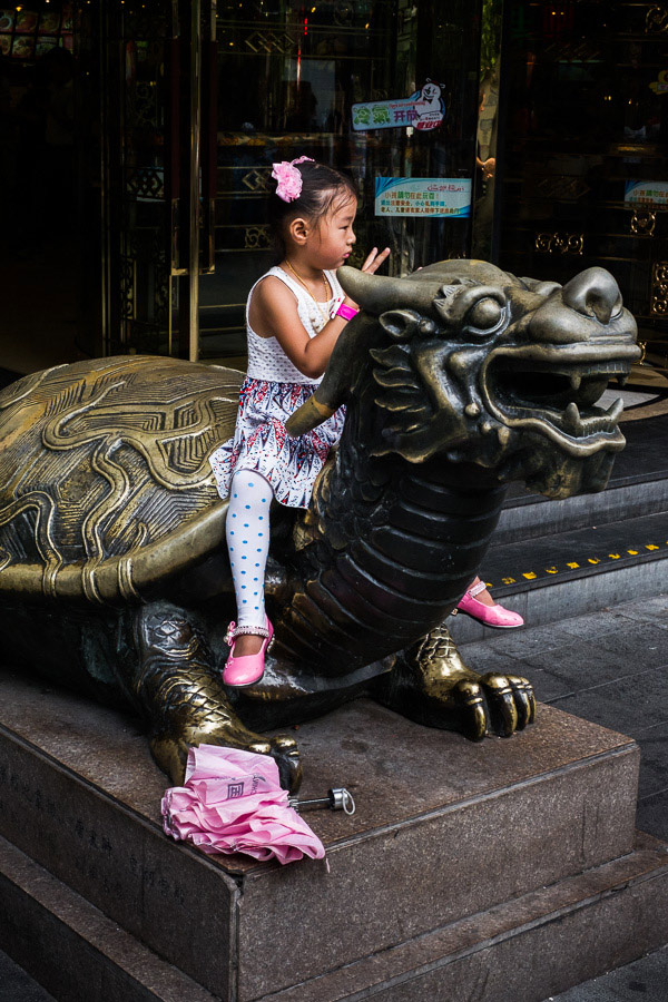 Street photo of child sitting on statue in Shanghai, China