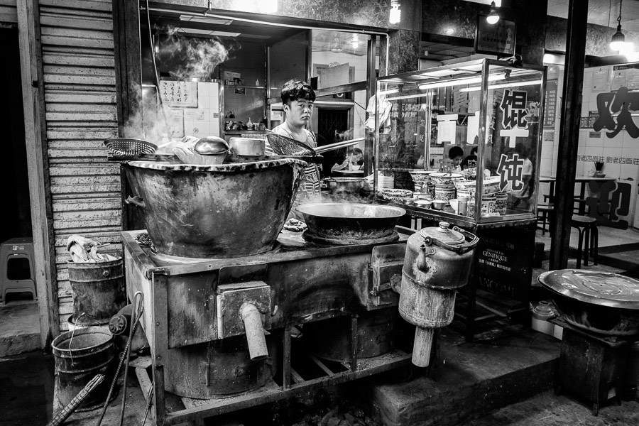 Street photo taken of man cooking food in Muslim quarter in Xi'an China