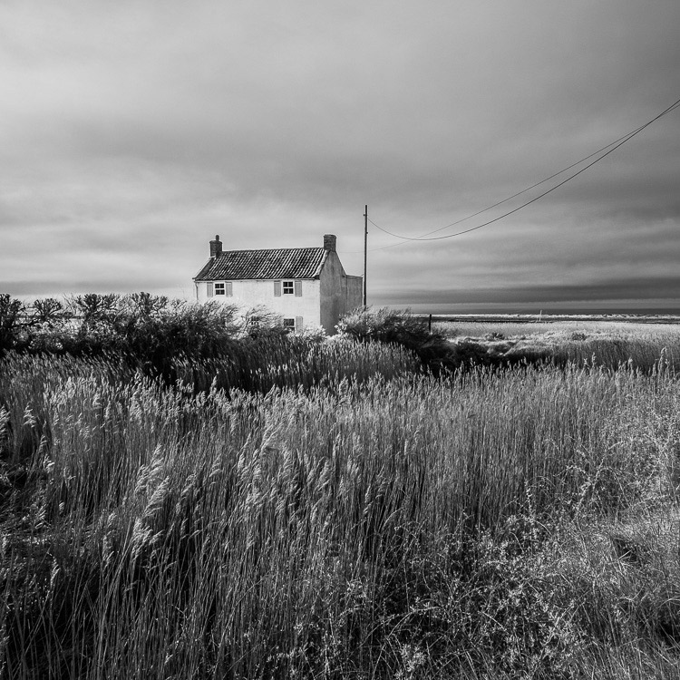 Black and white photo of an old house by the sea in Norfolk taken with a Fujifilm X-Pro 1 camera converted to infrared