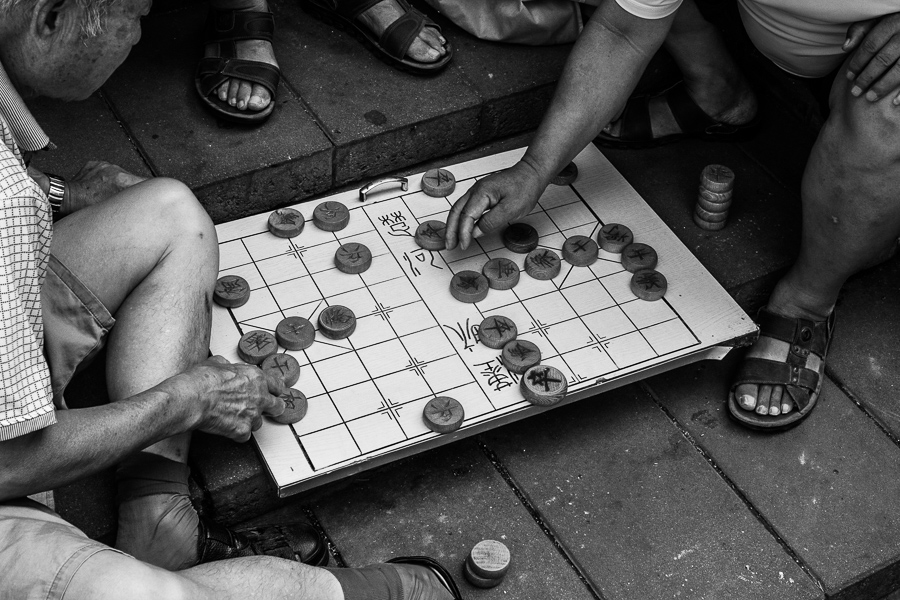 Black & white street photo of men playing xiangqi near the Temple of Heaven in Beijing, China