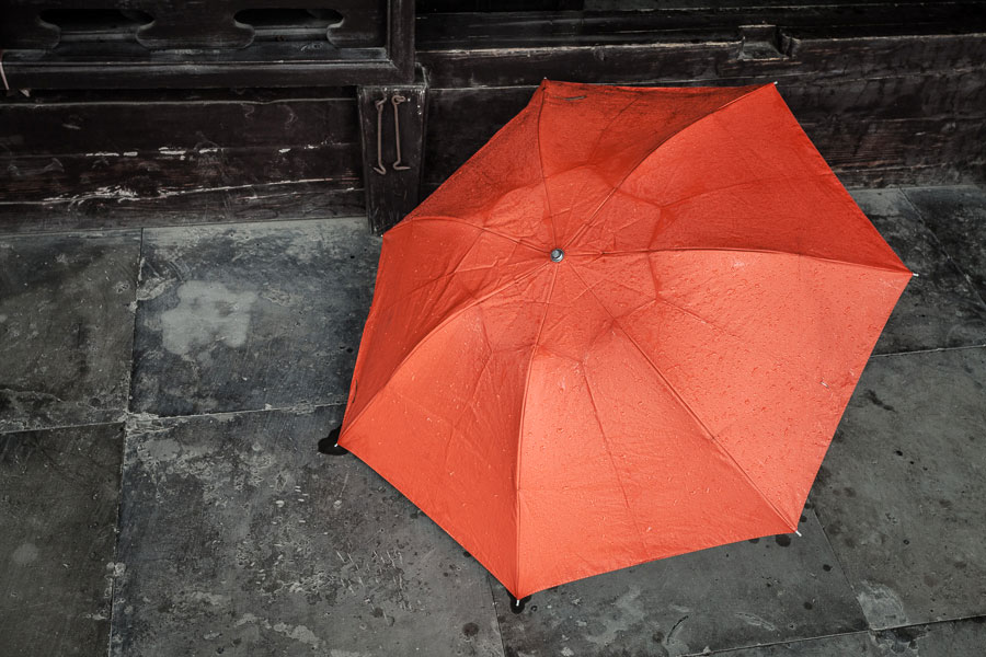 Street photo of orange umbrella