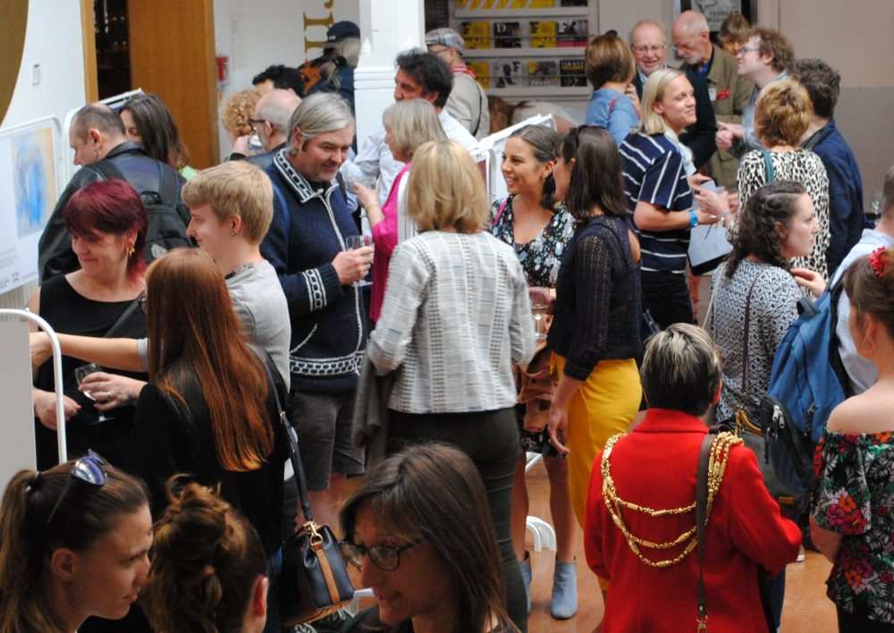 An image captured at the opening of Creative Future's online shop at Brighton Dome. The Mayor, Dominique De-LIght (Director of Creative Future) and local artists Yvonne J Foster are pictured speaking to the crowd at the exhibition launch.