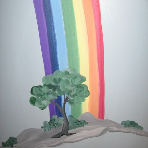 the rainbow ends behind a great tree