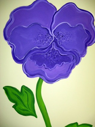 One of the many purple flowers , a large pansie.