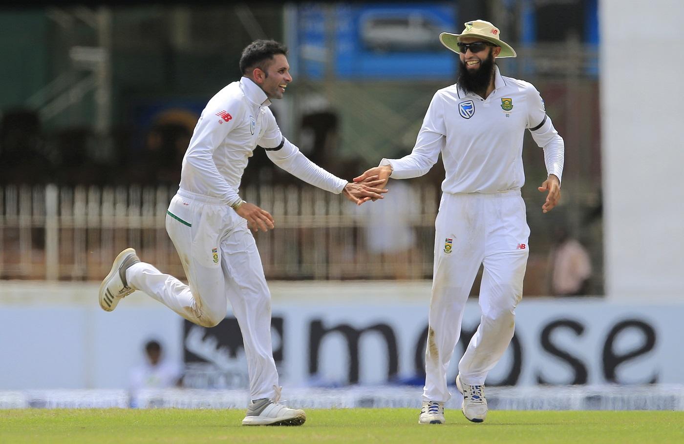 South African cricketers Keshav Maharaj, left, and Hashim Amla celebrate the dismissal of Sri Lanka's Danushka Gunathilaka