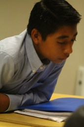 EL student leans in to what his tutors says in efforts to better hear
