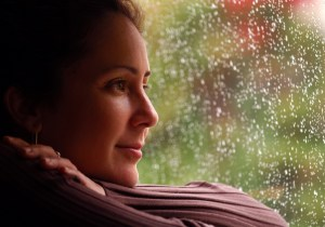 hopeful woman looking outside window while its raining