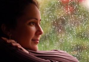 hopeful woman looking outside window while its raining