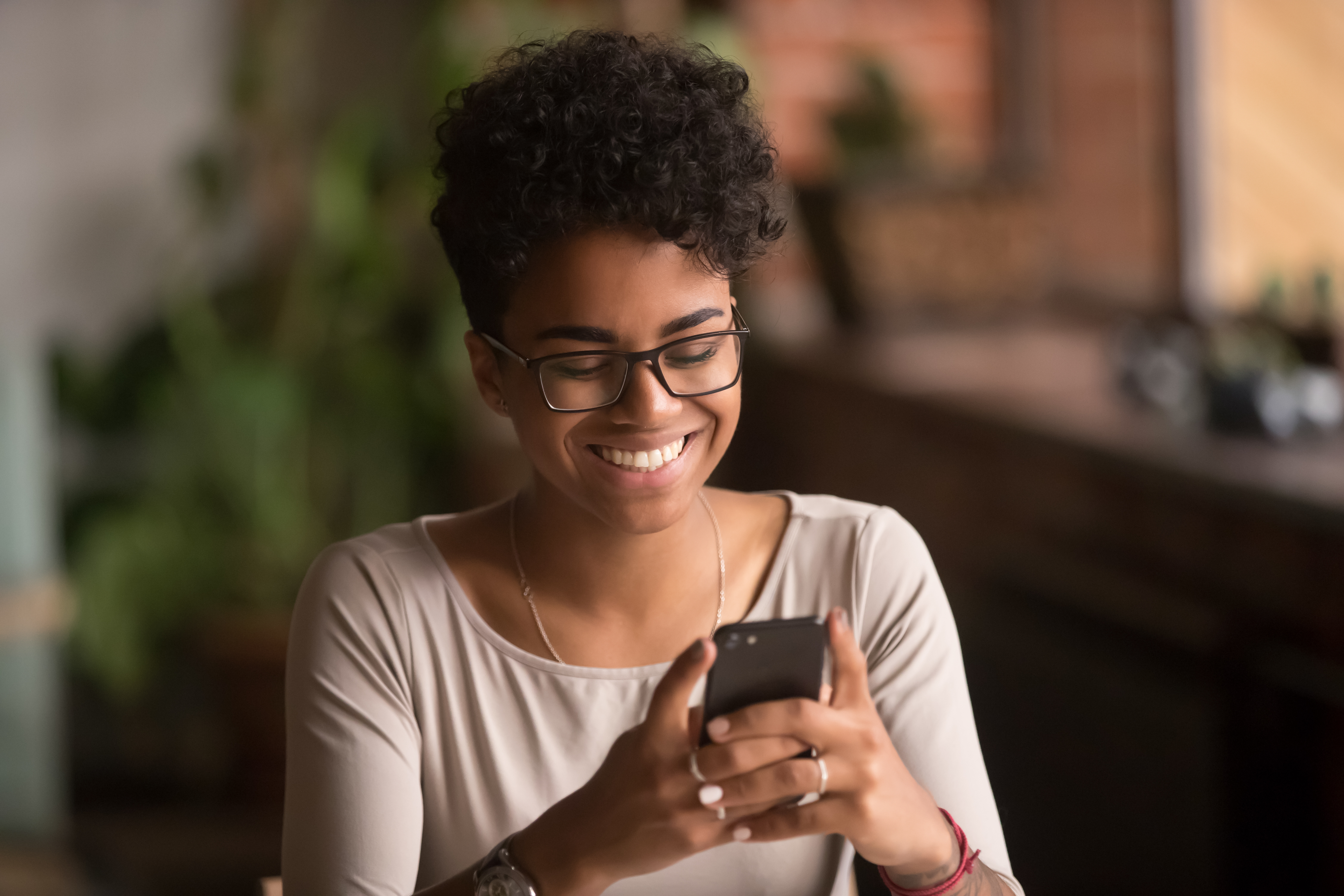 Happy millennial african american woman holding smartphone using ecommerce apps, playing mobile games, chatting in messengers or social media networks, surfing internet or texting message on phone