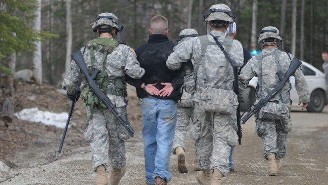 Alaska National Guard Soldiers escort a protestor away after assisting Anchorage Police to calm or detain rioters as part of the training scenario of exercise Vigilant Guard Ft. Richardson, Alaska, Wednesday April 28, 2010. Vigilant Guard is an annual, disaster-based training scenario that tests the coordination of National Guard units with local, state, regional, and national disaster preparedness organizations. (U.S. Air Force photo by Tech. Sgt. Brian E. Christiansen, North Carolina National Guard) (Released)