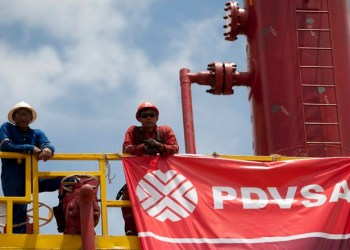 Workers stand in front of a drilling rig at an oil well operated by Venezuela's state oil company PDVSA in Morichal July 28, 2011.  Venezuela received an enviable honor last month: OPEC said it is sitting on the biggest reserves of crude oil in the world -- even more than Saudi Arabia.  But the Venezuelan oil industry is also sitting atop a well of trouble.  Picture taken July 28, 2011.  To match Special Report VENEZUELA/PDVSA  REUTERS/Carlos Garcia Rawlins (VENEZUELA - Tags: ENERGY POLITICS BUSINESS)