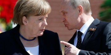 File photo of Russian President Vladimir Putin speaking with German Chancellor Angela Merkel