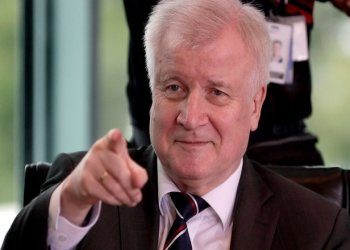 German Interior Minister Horst Seehofer points prior to the weekly cabinet meeting at the chancellery in Berlin, Germany, Friday, July 6, 2018. (AP Photo/Michael Sohn)