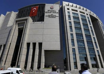 People stand outside a courthouse building in Istanbul, on Monday, Aug. 15, 2016. Police teams on Monday apprehended 136 personnel in operations conducted at three Istanbul courthouses as part of an investigation into the July 15 abortive coup. (AP Photo/Thanassis Stavrakis)