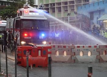 epaselect epa07792203 An anti-riot police vehicle equipped with a water cannon clears the road from a barricade set up by protesters during an anti-government rally in Kwai Fung and Tsuen Wan, Hong Kong, China, 25 August 2019. The protests were triggered last June by an extradition bill to China, now suspended, and evolved into a wider anti-government movement with no end in sight.  EPA/JEROME FAVRE