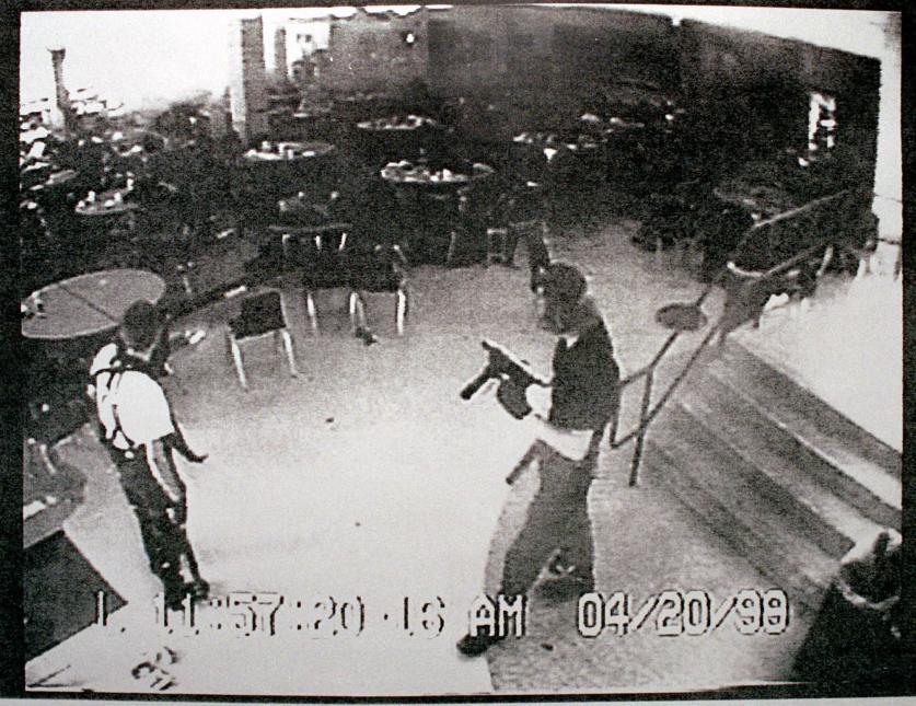 1999. Secundaria Columbine en Littleton, Colorado. Eric Harris y Dylan Klebold, dos jóvenes blancos de 18 años de edad, manejaban un sitio web donde publicaban instrucciones para fabricar bombas y sus ideas antisociales. Planificaron meticulosamente un ataque en el que pretendían disparar a los sobrevivientes de dos bombas que habían plantado dentro de la escuela. Los artefactos no explotaron, pero la pareja disparó contra varios de sus compañeros de secundaria durante casi una hora hasta que se suicidaron. Asesinaron a 15 personas. En la fotografía Eric Harris y Dylan Klebold captados por cámaras de seguridad, en la cafetería de la secundaria Columbine durante el tiroteo. 20 de abril de 1999.