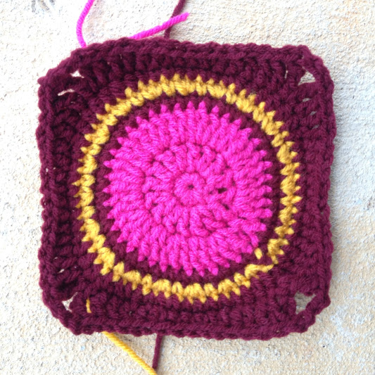 Crochet granny square with a bright pink round center