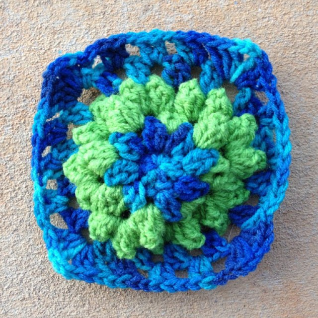 Variation on a crochet granny square in bright green and variegated blue