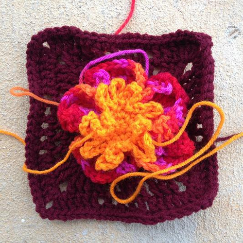 Crochet granny square with the crochet flower pieces arranged on top