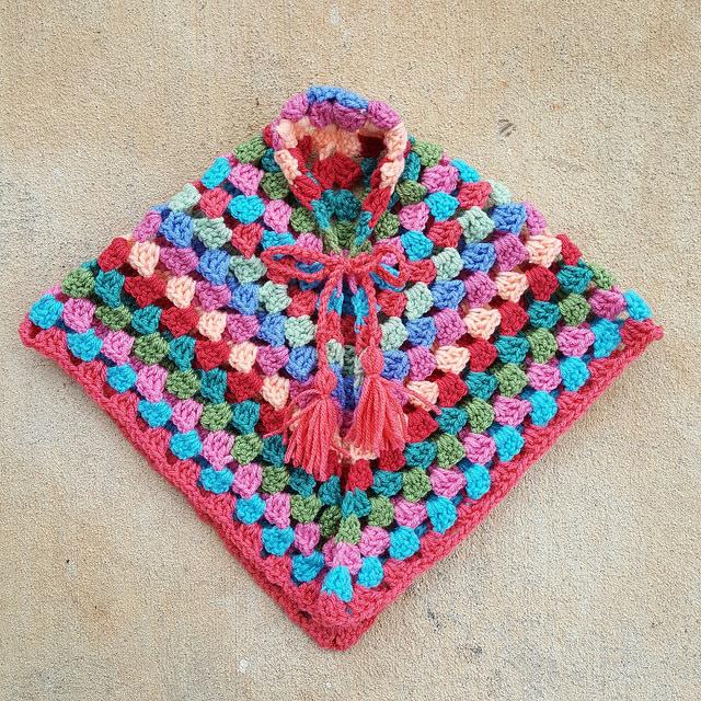 A multicolor granny square stitch crochet poncho for a child