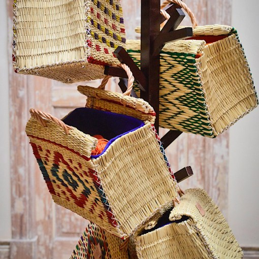 several CESTA reed project baskets hanging on coat rack