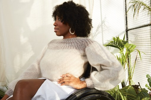 black woman in wheelchair modelling white fluffly lace mohair sweater