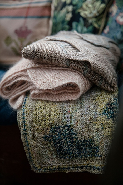 A stack of folded shawls from the Laine Publishing - 52 Weeks of Shawls