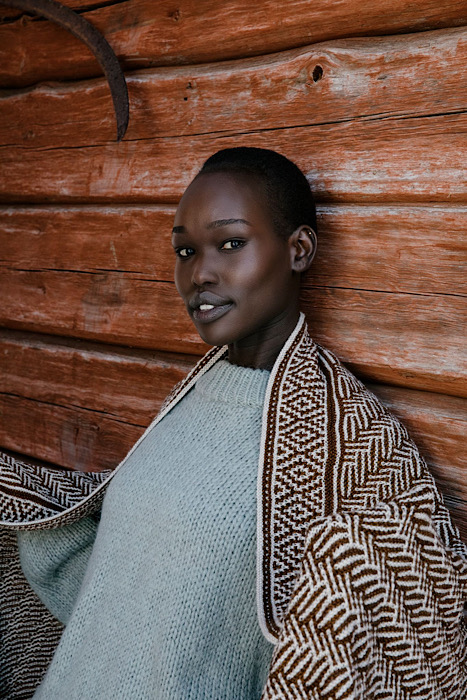 Black woman modeling a color work shawl of Laine Publishing - 52 Weeks of Shawls