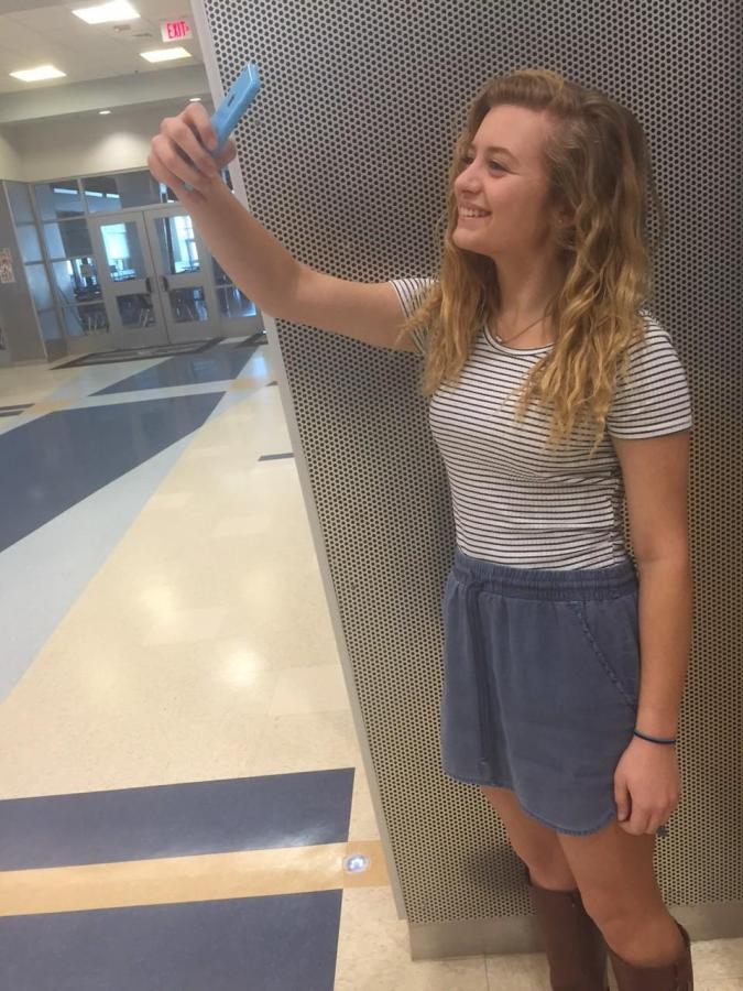 Junior+Carolyn+Bradley+uses+her+iPhone+to+take+a+selfie+and+post+it+on+her+Snapchat+story