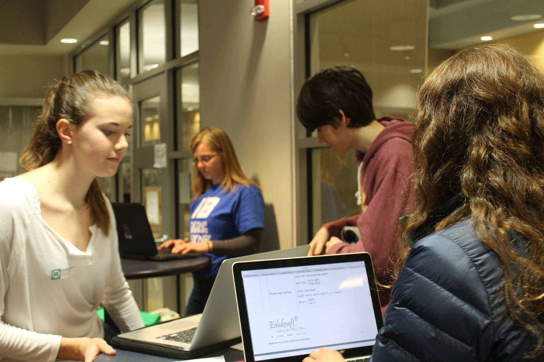 Junior Claire Pfeifer works with her group to help solve the school wifi issues.