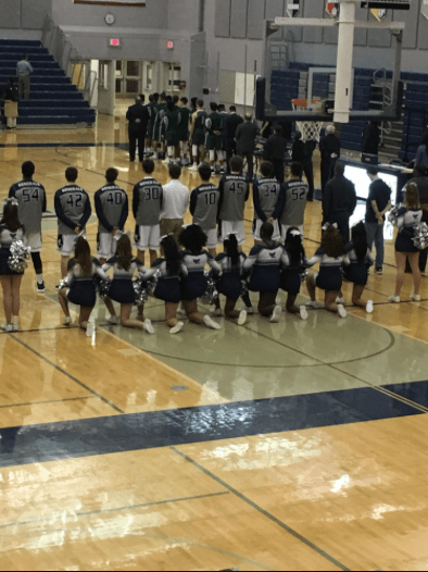 Nine cheerleaders kneel during the national anthem, while the rest of the team and the basketball team stands