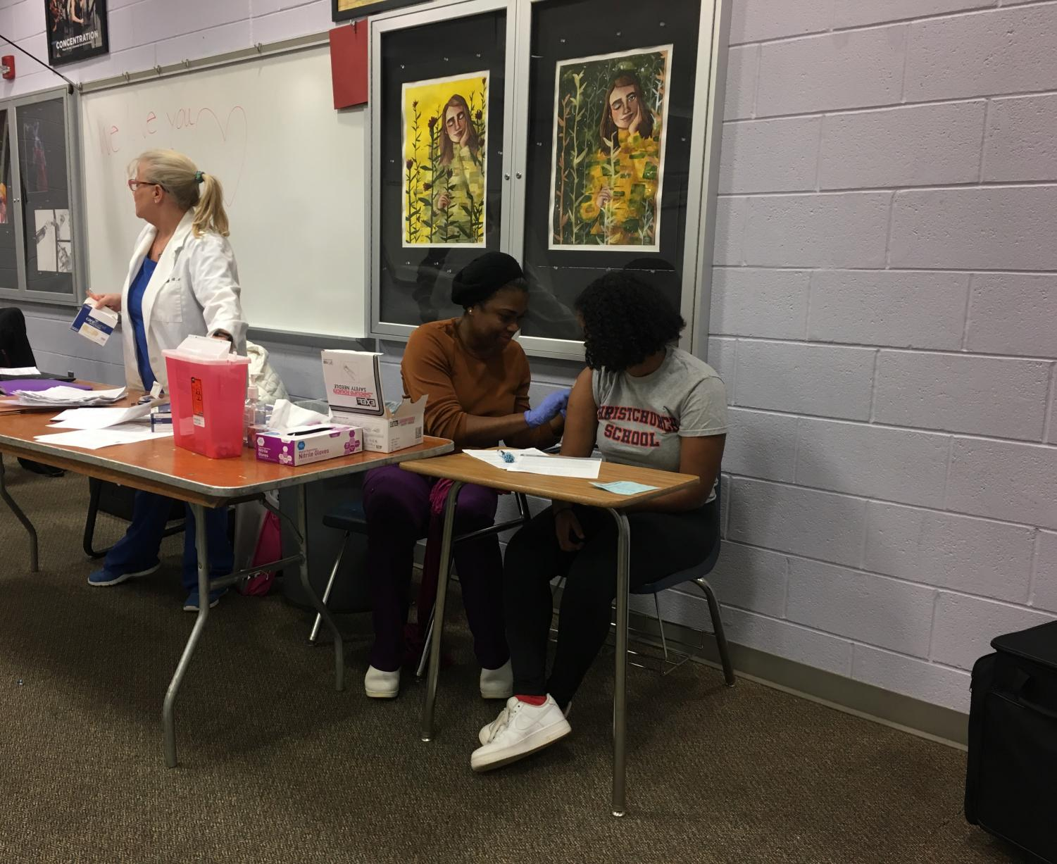 Junior Kalki Ausink receiving her annual flu shot from Medical Advisor Ms. Dorothy Cyphers, while other Medical Advisor Ms. Diane Lekang prepares for the next student.