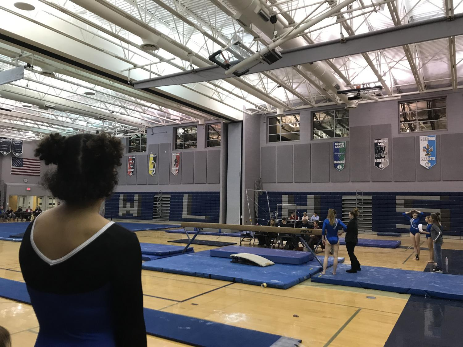 Freshmen Sophia Bailey looks over the gymnastics events being held at the school, waiting for her turn on vault. This is the schools first home meet of the season against four other competing schools.