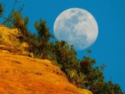 Full moon rising over red cliffs to view the moon and connect with its energy.