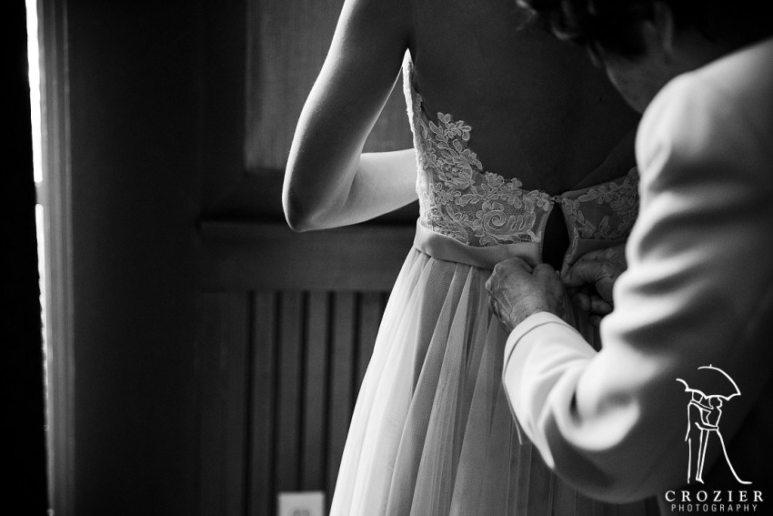 bride has her dress laced