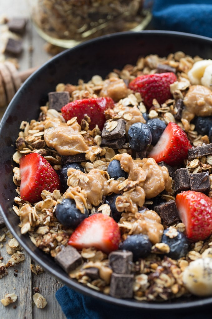 Up-close overhead view of granola and fruit in a black bowl on a wood surface.