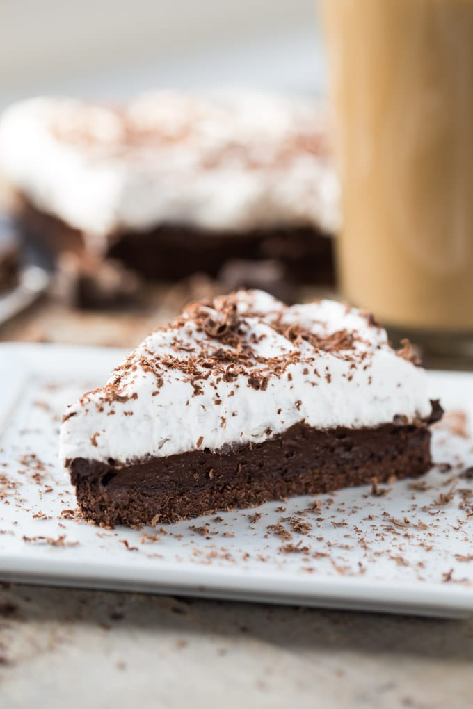 Side view of a slice of Dark Chocolate Irish Whiskey Tart on a white plate with the full tart and cup of coffee in background.