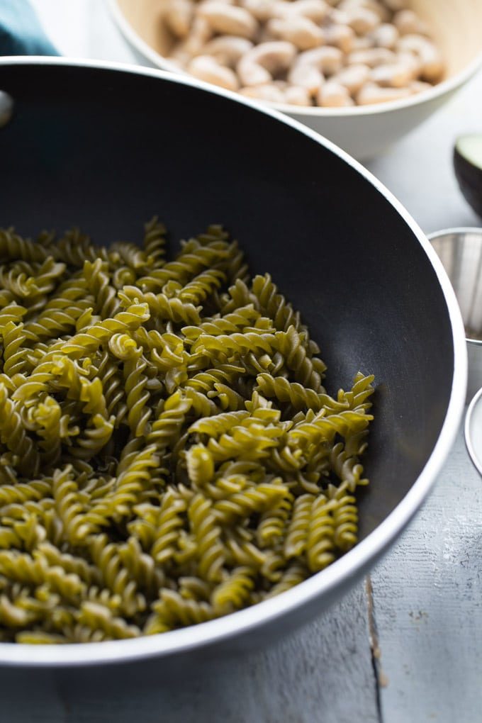 Uncooked pea flour rotini in a black pan on white wooden surface with bowl of cashews in background.