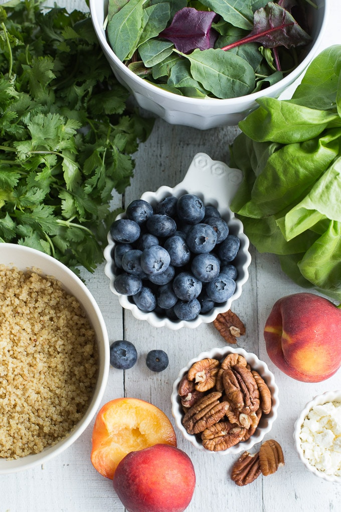 Ingredients for a Blueberry Peach Quinoa Salad arranged on a white wooden surface.