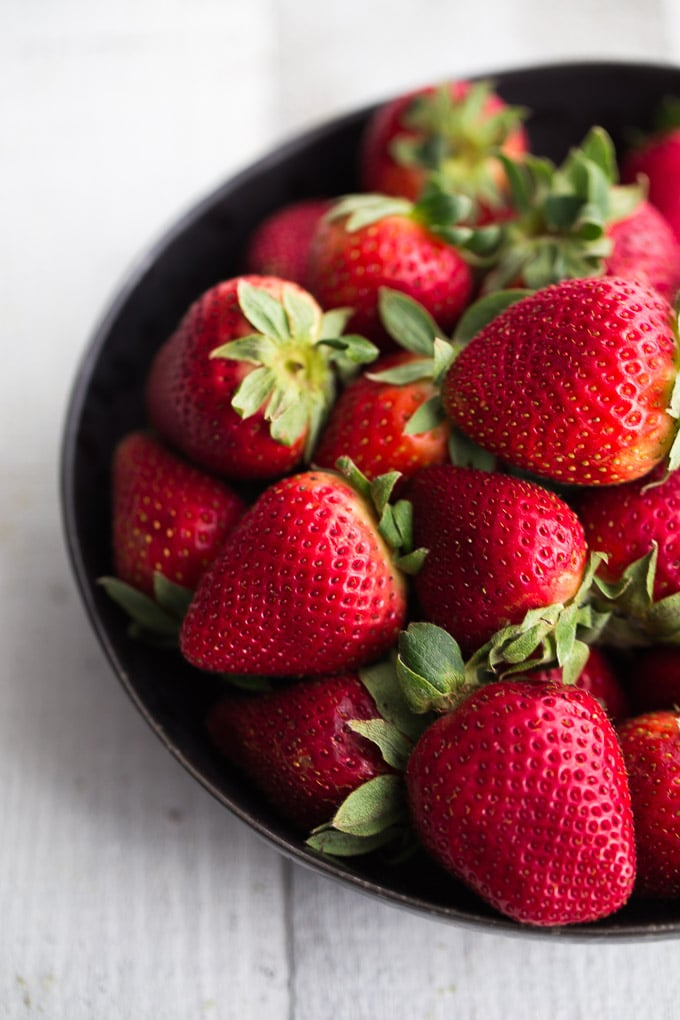 Fresh strawberries in a black bowl on a white surface.