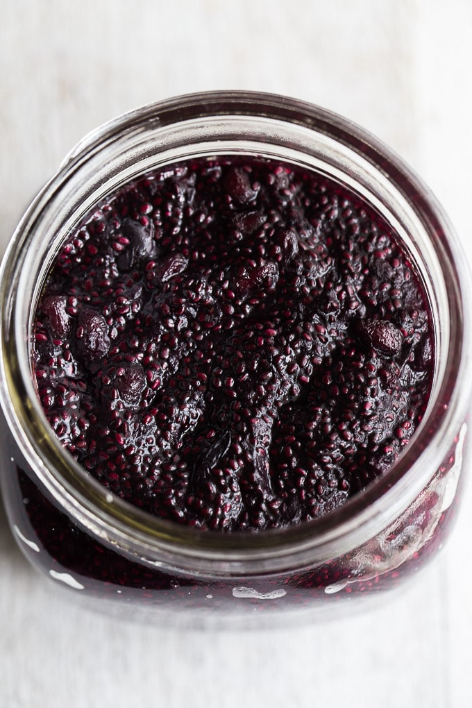 Up-close overhead view of Blueberry Pomegranate Chia Jam in a glass jar.