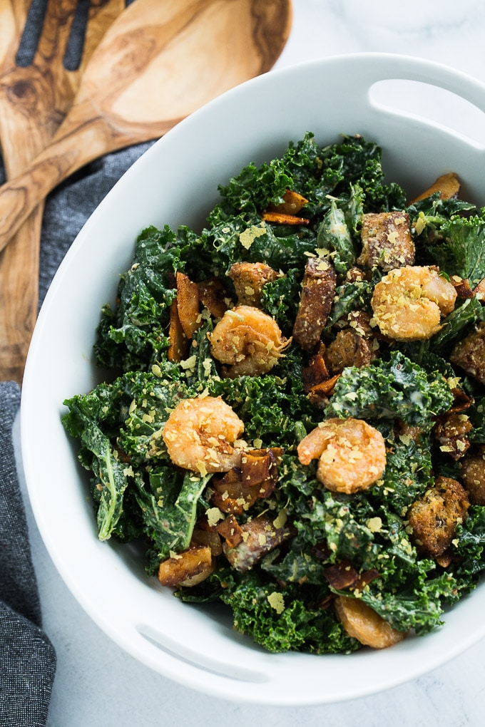 Up-close, overhead view of Kale Caesar Salad in a white bowl next to wooden serving spoons.