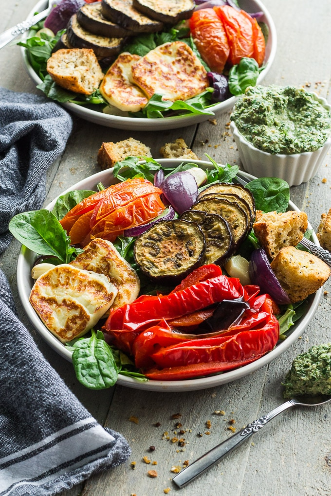Up-close view of two plates of Salad with Roasted Vegetables and Halloumi Cheese next to a cup of pesto on a wooden surface.