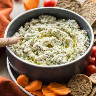 Creamy Cashew Onion Herb Dip in a bowl surrounded by crackers, cherry tomatoes and carrot slices.